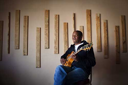 Jazz guitarist, Mac McKenzie, is photographed in the bedroom of his home in Athlone outside of Cape Town, South Africa.